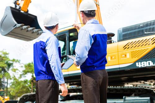 Plakat Azjatycki inżynier dyskutuje plany na budowie