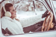 Driving A Car At Wintertime - Pretty, Young Woman Driving Her Vintage VW Beetle Car At Snowy Road, Color Toned Image