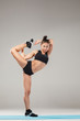 Beautiful sporty girl standing in acrobat pose or yoga asana