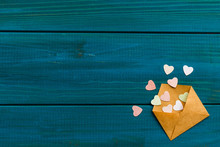 Blue Wooden Background For Valentine's Day With Pink Hearts In The Envelope