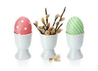FototapetaColorful easter eggs in egg cup, with pussy-willow. Isolation on a white background