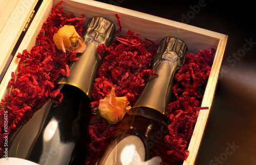 Fototapeta Skrzynka z butelkami szampana i żółte róże. obraz
