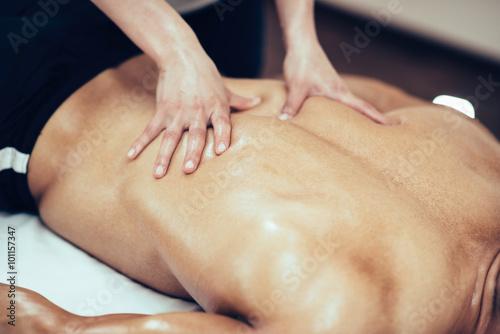 Zdjęcie XXL Masaż sportowy. Terapeuta masuje plecy