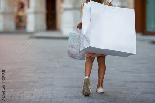 Little girl walking with shopping bags outdoors in european city
