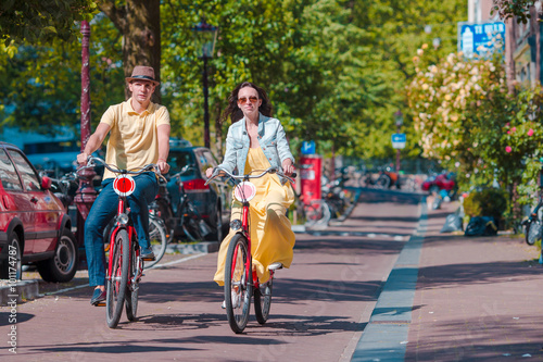 Photo  Young happy caucasian couple on bikes in old streets in Amsterdam