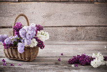 Basket With A Branch Of Lilac Flower On A Wooden Background