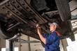 Car mechanic examining lifted car at repair service station. Usi