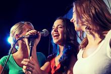 Happy Young Women Singing Karaoke In Night Club