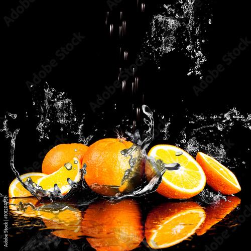 pomarancze-w-kroplach-wody-na-czarnym-tle