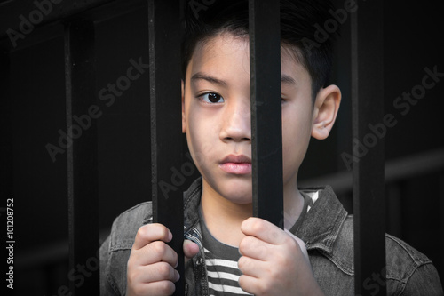 Fotografie, Obraz  asian boy Hand in jail looking out the window