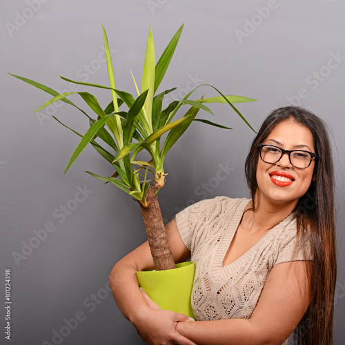 Valokuva  Beautiful happy woman holding plant in vase against gray backgro