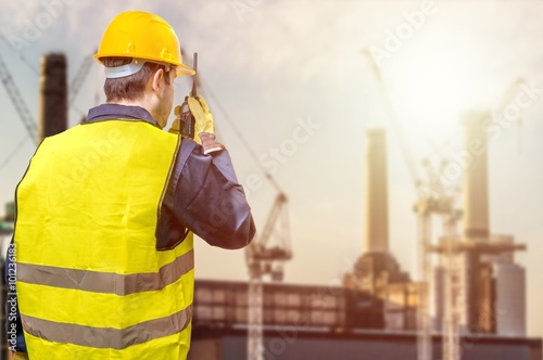 Photo  Worker is using radio and crane site during sunset