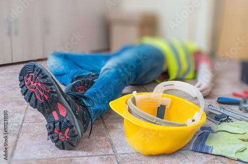 Obraz Leg and yellow helmet of injured lying worker at work. - fototapety do salonu