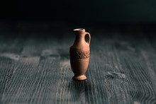 Small Clay Jug On A Wooden Table
