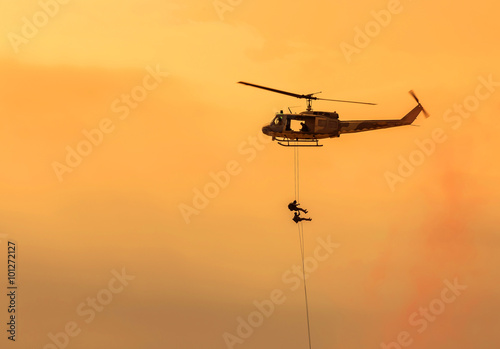 plakat soldiers climb down from helicopter in military mission.