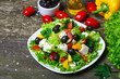 Greek salad with fresh vegetables, feta cheese and black olives on a wooden background