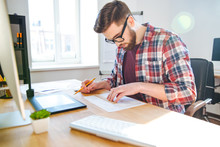 Portrait Of Young Male Designer Sitting And Making Blueprint