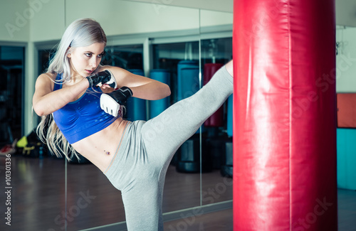 Foto op Plexiglas Vechtsport Woman hits the heavy bag with a strong kick