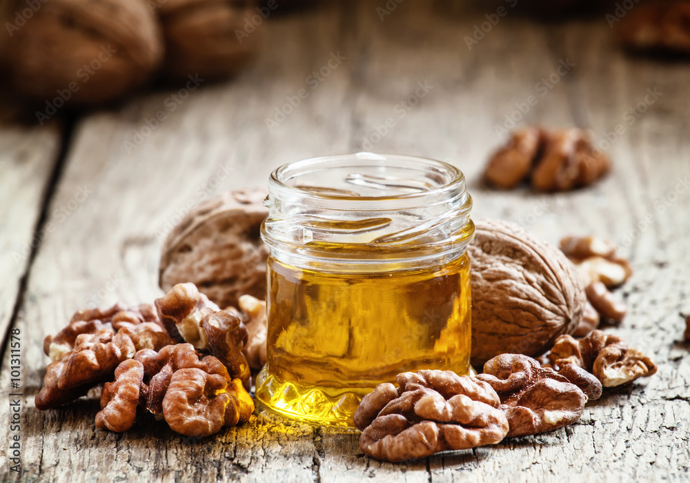Fototapety, obrazy: Walnut oil in a small jar and kernels on old wooden background i