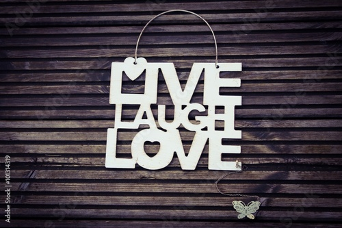 Metal sign with the words LIVE LAUGH LOVE with a metal butterfly on a wooden sur Canvas Print