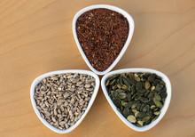 Eatable Seeds (sunflower, Pumpkin, Flax) In Three Bowls Arranged In A Three-leaf Shape, Top View