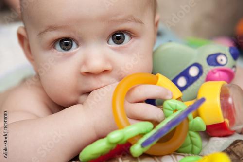 Ребенок с игрушками лежит на кровати