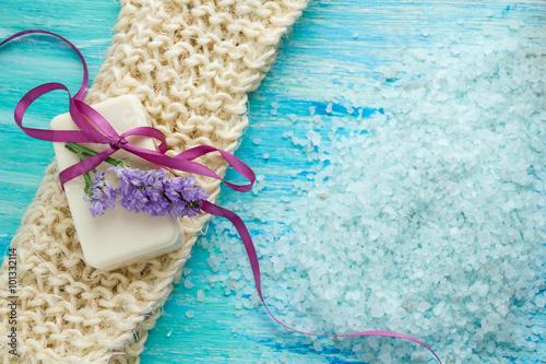 Fototapeta natural organic soap  and sea salt   on a blue wooden table, Spa with flowers obraz na płótnie