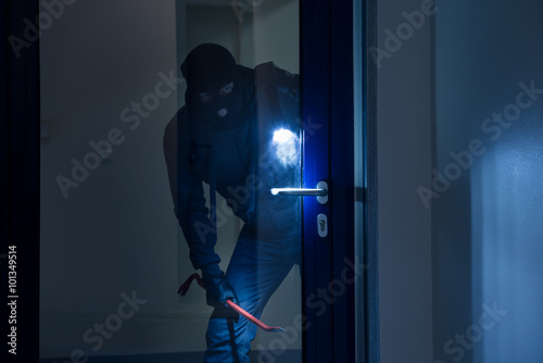 Fotografía Thief With Flashlight Trying To Break Door