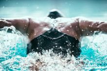 Butterfly Stroke Swimming Champion In Action. Powerful Thrust Forward. Shot From Behind, Focus On Water Ripple Behind The Swimmer