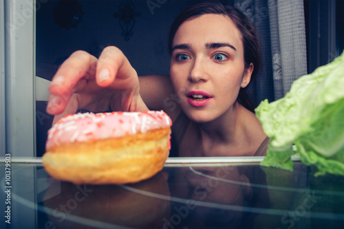 Fotomural Hungry cute female reaches for donut at night near fridge