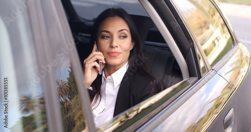 Photographie  Beautiful young business woman with long hair in conversation on phone while sit