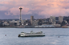 Seattle Skyline. A Ferryboat Cruises Past The Space Needle And The The Seattle Waterfront During A Lovely Sunset.