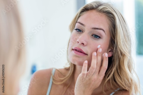 Fotografie, Obraz  Smiling pretty woman applying cream on her face
