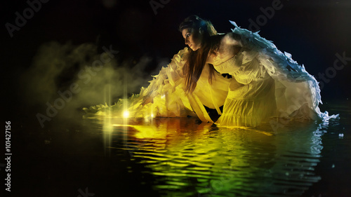 Valokuva  Beautiful white angel is standing in the magic water.