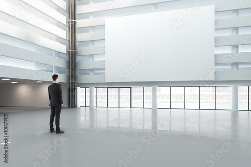 Poster Graffiti man looking at a blank white banner in a large bright hall, mock
