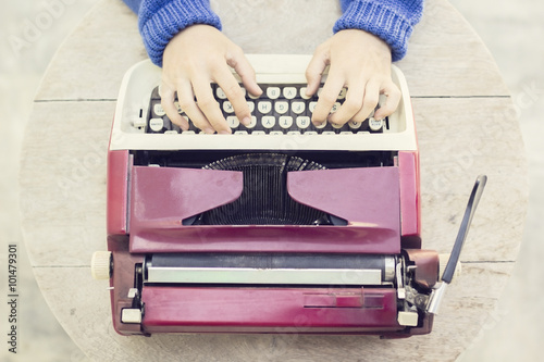 Papiers peints Retro Top view on the girl with vintage typewriter on wooden table