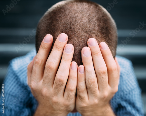 Fotografía Closeup portrait of despaired young man covering his face with hands