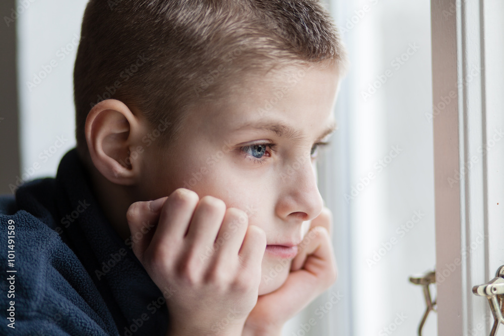 Fototapeta Pensive Boy Leans his Face on Hands at the Window