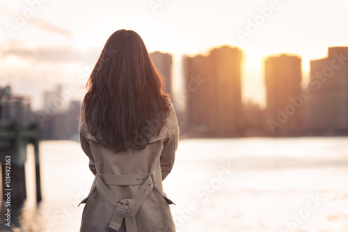 Photo  Beautiful lonely girl waiting for somebody bear the water at sunset time