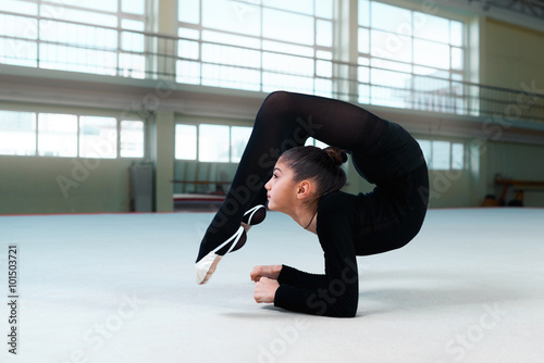 gymnast performs a back bend on  floor Canvas Print