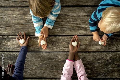 Fotografía  Vista superior de cuatro niños de razas mixtas cada uno con una canica h