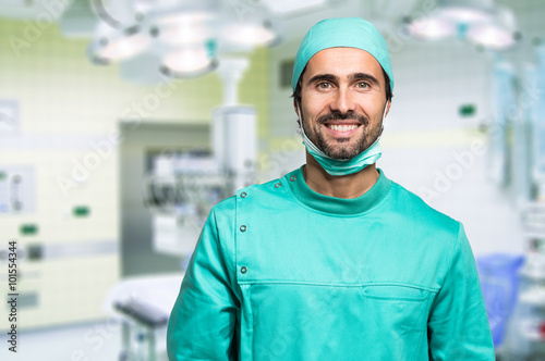 Fotomural Smiling surgeon crossing his arms while standing in a surgical room