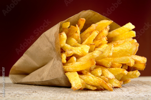 Poster de jardin Buffet, Bar French fries in the paper bag on burned background on wooden table