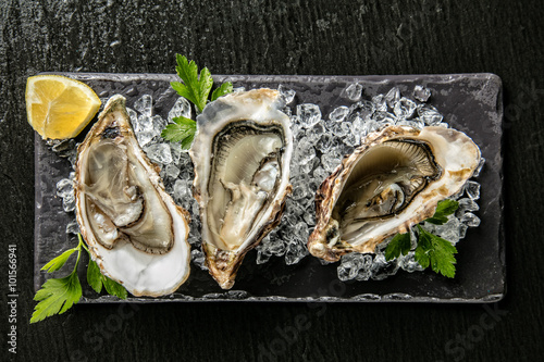 Poster Schaaldieren Oysters served on stone plate with ice drift