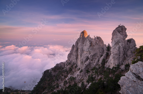 Fotobehang Grijze traf. Top of the mountains. High rocks with low clouds at sunset. Colorful nature background