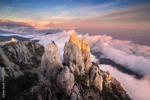 Foto op Aluminium Zalm Top of the mountains. High rocks with low clouds at sunset. Colorful nature background