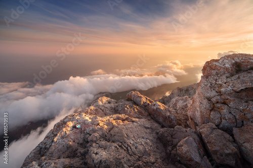 Beautiful landscape on the top of mountains with low clouds at sunset. Nature background