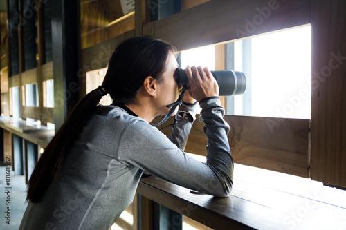 Valokuva  Woman watching bird though binocular