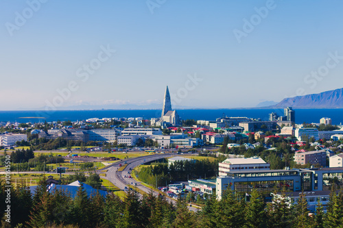 Fototapeta Beautiful super wide-angle aerial view of Reykjavik, Iceland with harbor and skyline mountains and scenery beyond the city, seen from the observation tower of Hallgrimskirkja Cathedral