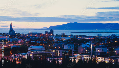 Fotografija  Beautiful super wide-angle aerial view of Reykjavik, Iceland with harbor and skyline mountains and scenery beyond the city, seen from the observation tower of Hallgrimskirkja Cathedral